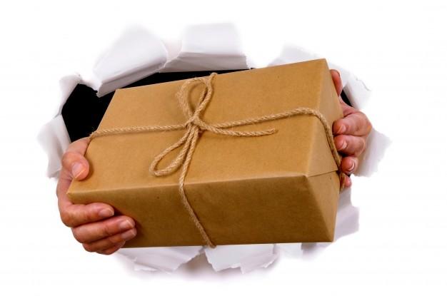 manos-que-entregan-un-paquete-a-traves-de-fondo-de-papel-rasgado-blanco_1101-299